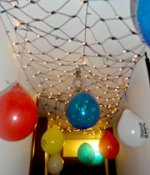 birthday balloons and star wars ballons hanging from our ceiling in a white lights net of 'stars'